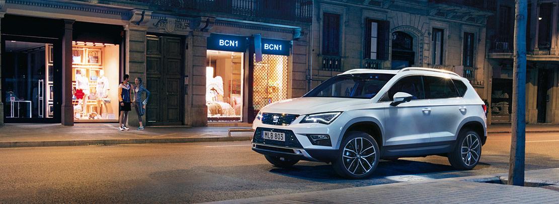 En SEAT i stadsmiljö på kvällen. Bilen står parkerad vid en trottoar utanför en butik.