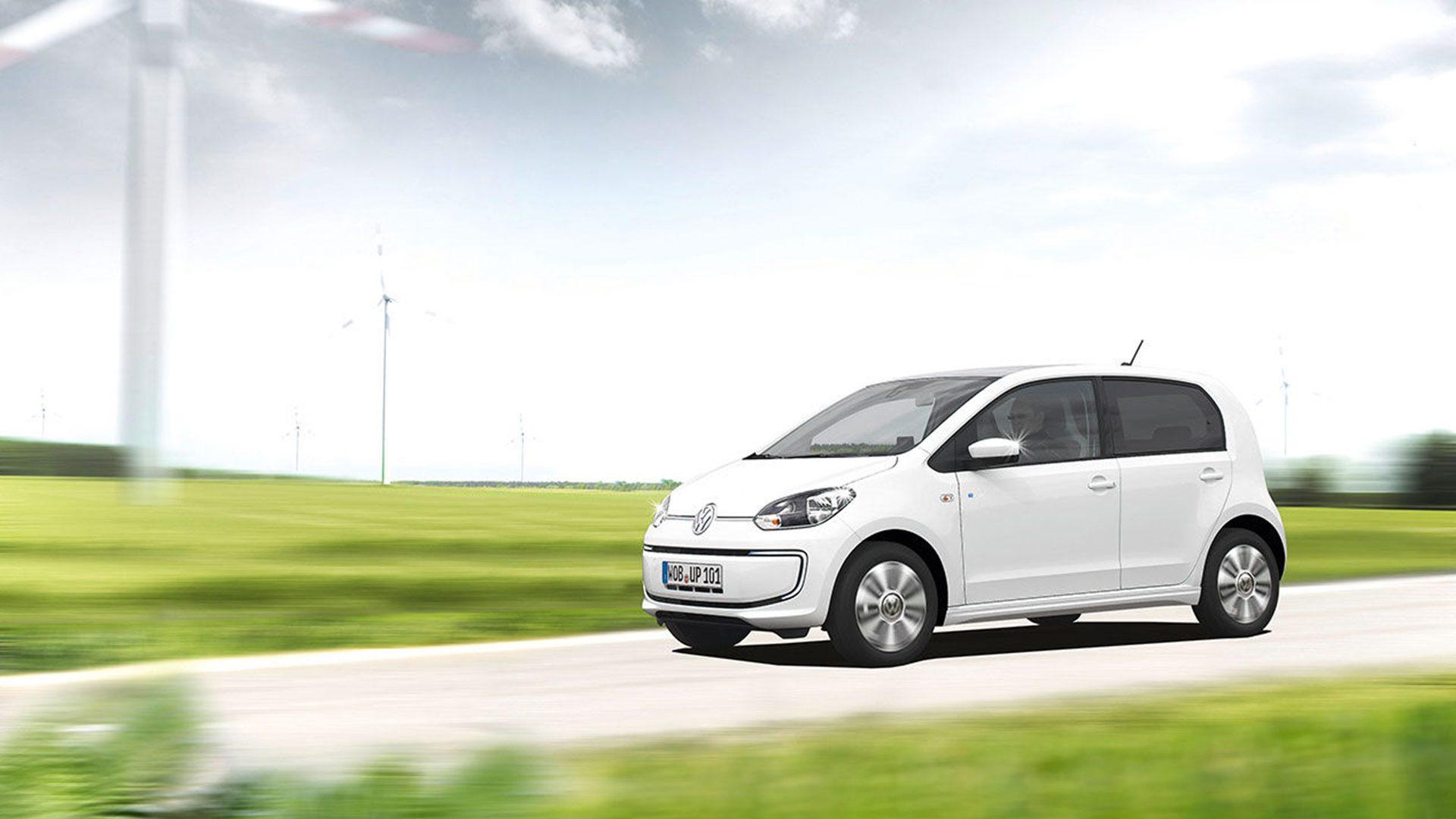 En Volkswagen up! kör på en väg med vindkraftverk i bakgrunden