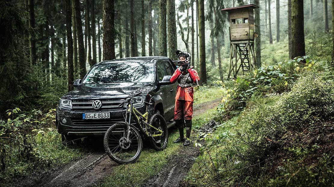 Volkswagen Amarok i skogen med mountainbikecyklist