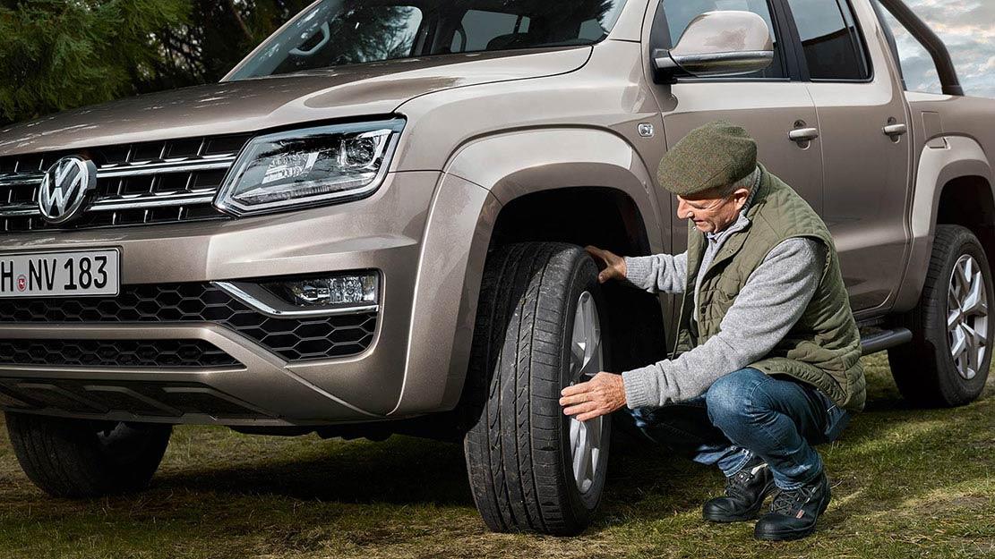 Man kontrollerar däcken på en Volkswagen Amarok