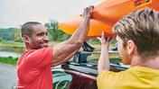 Två män lastar en kanot på takräcket på en VW.