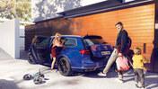 Familj vid blå VW Passat med öppen baklucka.