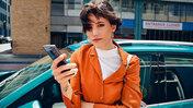 Kvinna med smartphone lutar sig mot turkos VW-bil