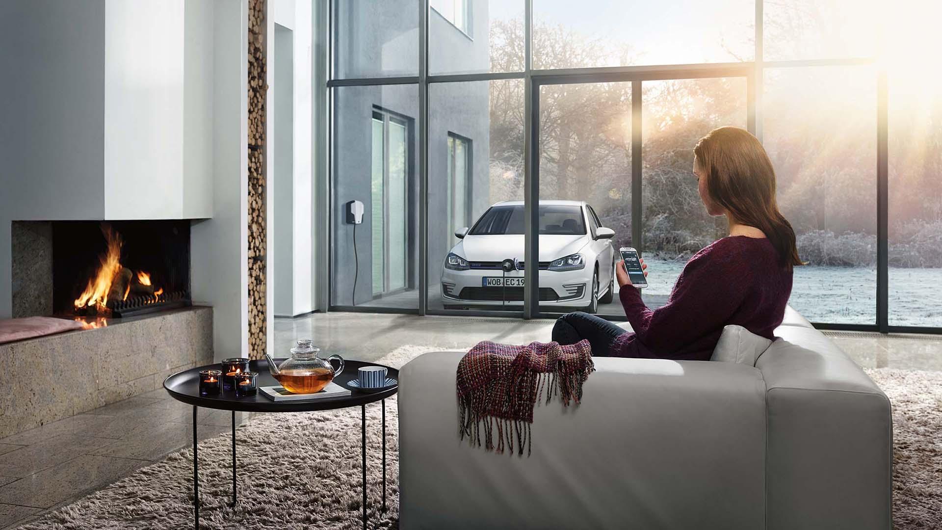 Kvinna vid eldstad som läser Das WeltAuto-artiklar i mobilen